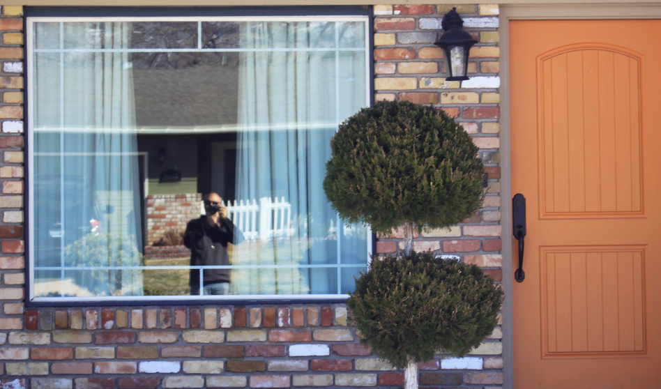 Reflection of Dominic Martinelli in window of brick house with orange door