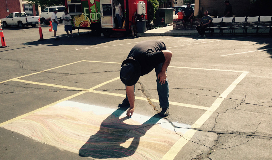 Dominic Martinelli drawing with chalk in a parking lot